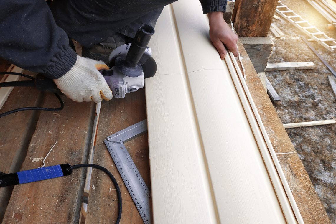 An employee cuts siding to the required size
